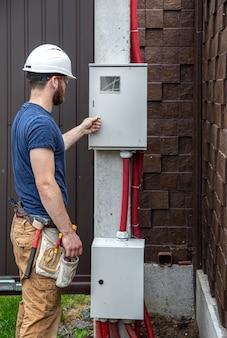 Электрик-строитель за работой, осматривает кабельное соединение в линии электропередачи в фюзеляже промышленного распределительного щита.