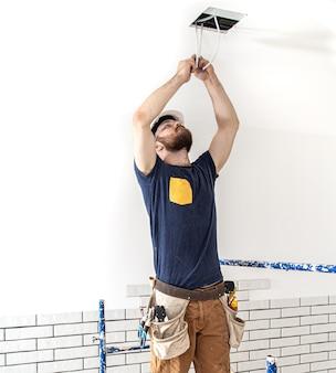 仕事中の電気技師ビルダー、高さでのランプの設置。修理現場のオーバーオールのプロ。