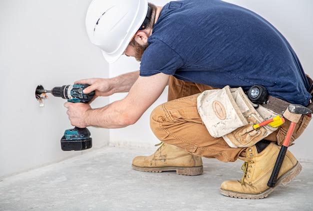 仕事中の電気技師ビルダー、高さでのランプの設置。ドリルでオーバーオールのプロ。修理現場の背景に。プロとして働くというコンセプト。