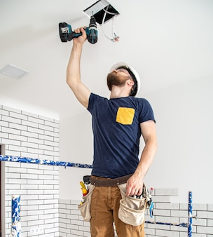 仕事中の電気技師ビルダー、高さでのランプの設置。修理現場でのドリルによるオーバーオールの専門家。