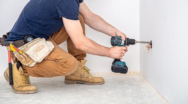 Электрик-строитель за работой, установка светильников на высоте. профессионал в спецодежде со сверлом.