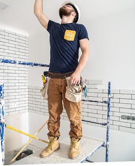仕事中の電気技師ビルダー、高さでのランプの設置。