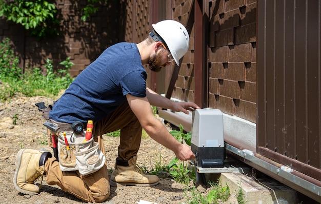 Электрик-строитель за работой, обслуживает промышленный распределительный щит фюзеляжа.