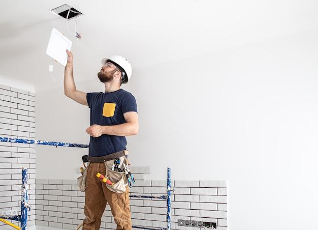 仕事中の白いヘルメットにひげを生やした電気技師ビルダー、高さにランプを設置。修理現場の背景にドリルでオーバーオールの専門家。