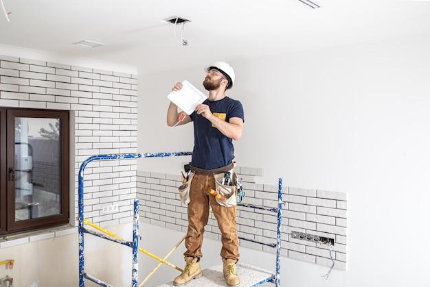 職場で白いヘルメットをかぶったあごひげを生やした電気技師ビルダー、高所にランプを設置。修理現場でのドリルによるオーバーオールの専門家。