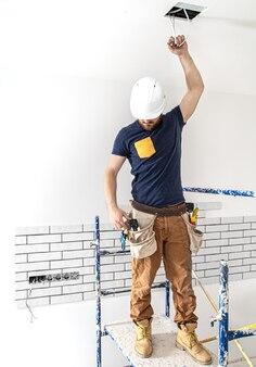 仕事中の白いヘルメットをかぶった電気技師ビルダーの労働者、高所にランプを設置。修理現場のオーバーオールのプロ。