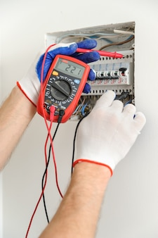 Electrician check voltage in electrical fuse box.