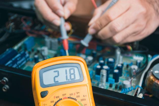 디지털 멀티미터로 전자 회로 기판의 전압을 확인하는 전기 기술자
