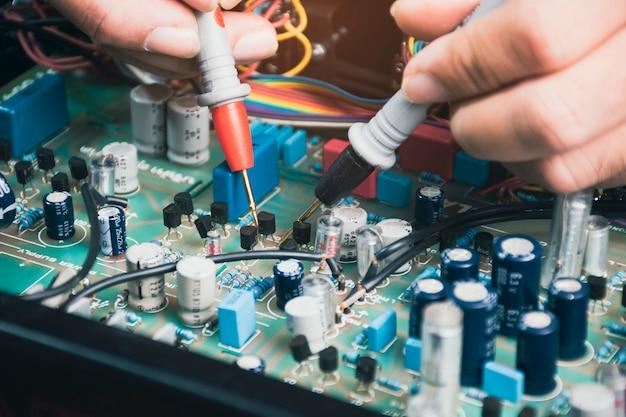 디지털 멀티미터 프로브가 있는 전자 회로 기판의 트랜지스터 전압을 확인하는 전기 기술자