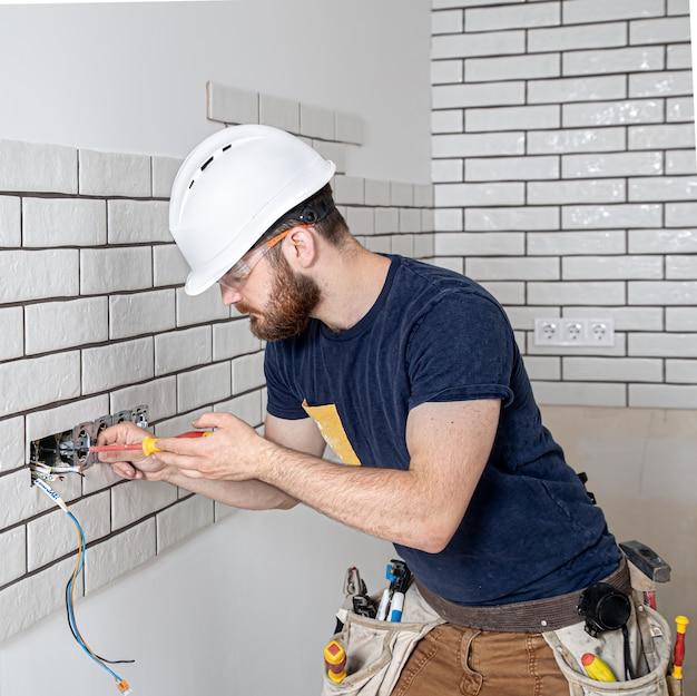 소켓을 설치하는 동안 작업 바지에 수염을 가진 전기 건설 노동자. 홈 리노베이션 개념.