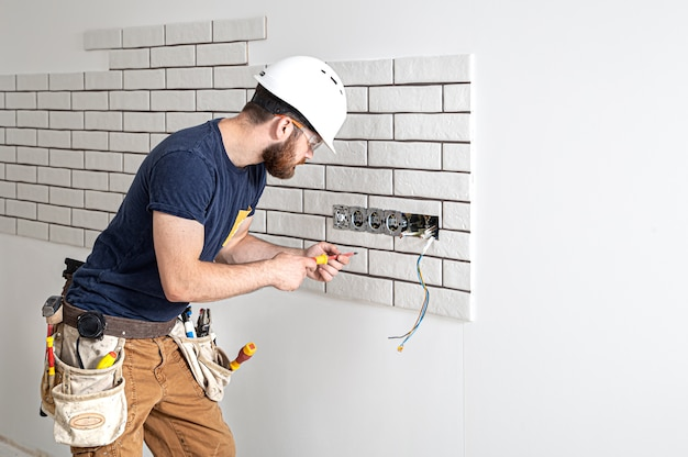 Electrician construction worker with a beard in overalls during the installation of sockets. home renovation concept.