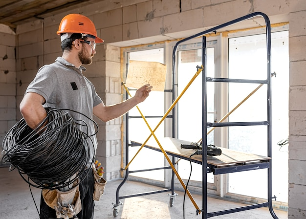 Electrician contractor in a sunny room holds an electric cable copy space.