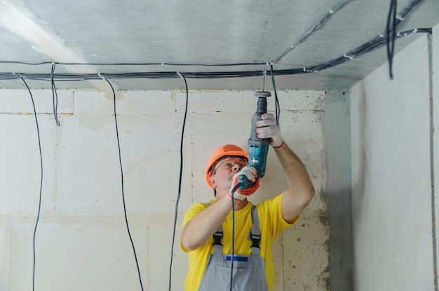 전기 케이블을 고정하기 위해 천공기로 천장을 시추하는 전기 기술자