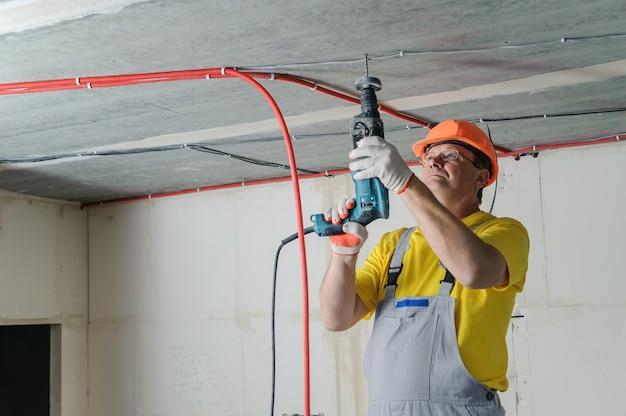 골판지 파이프를 고정하기 위해 천공기로 천장을 뚫는 전기 기사