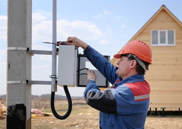 Электрик занимается установкой электросчетчика на опорах лэп. процесс электрика. вид сбоку на дом