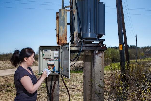 Женщина инженер-электрик проверяет счетчик электроэнергии и счет-фактуру.