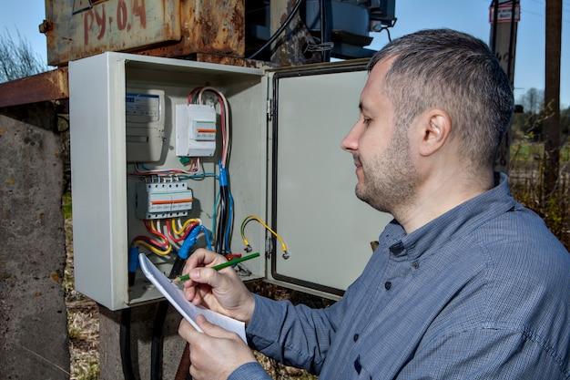 クリップボードに電気メーターの読みを書く電気技師。