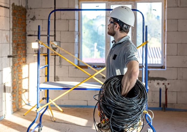 An electrician examines a construction drawing while holding an electrical cable in his hand at a work site.