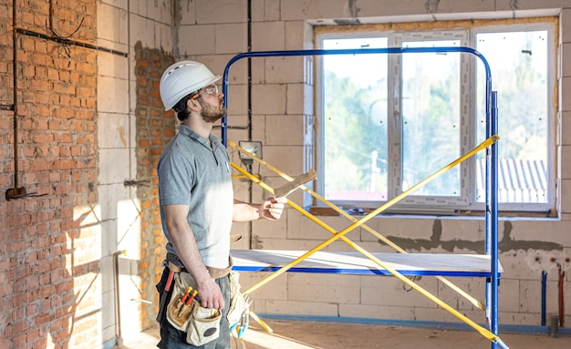 An electrician examines a construction drawing at a work site.