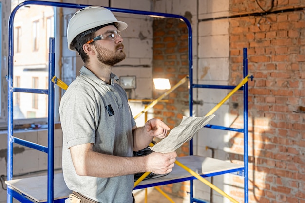 An electrician examines a construction drawing at a work site