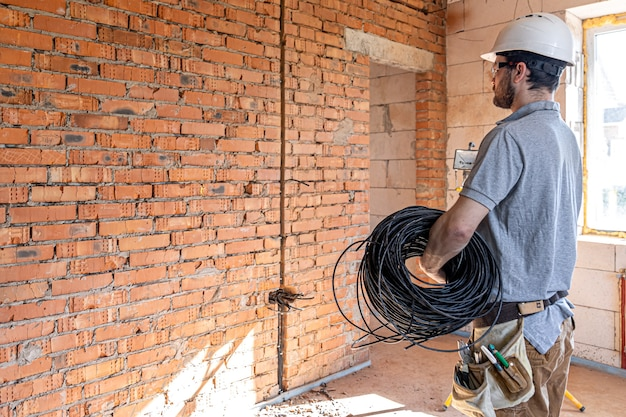 An electrician examines a construction site while holding an electrical cable in his hand at the work site.