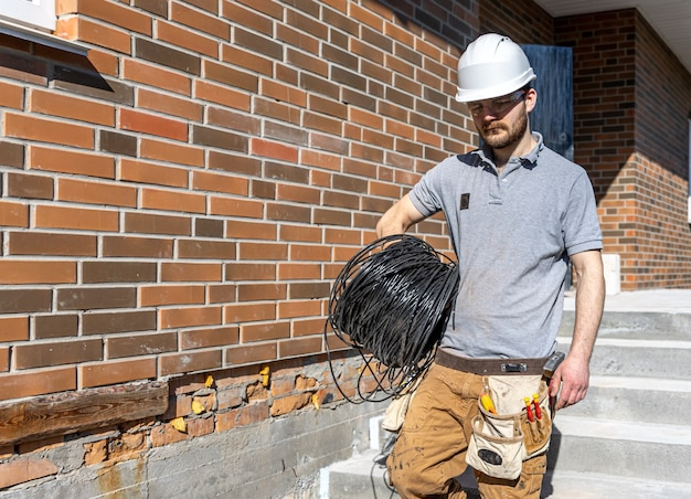 An electrician examines a construction site while holding an electrical cable in his hand at the worksite