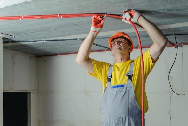 전기 골판지 튜브를 천장에 고정하는 전기 기술자