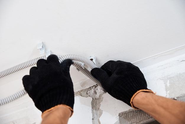 Электрик крепления электрического кабеля к стене