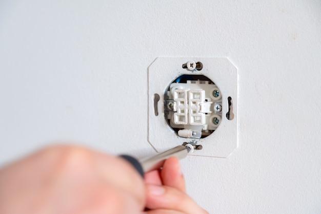 Электрик, фиксируя электрическую розетку с помощью отвертки