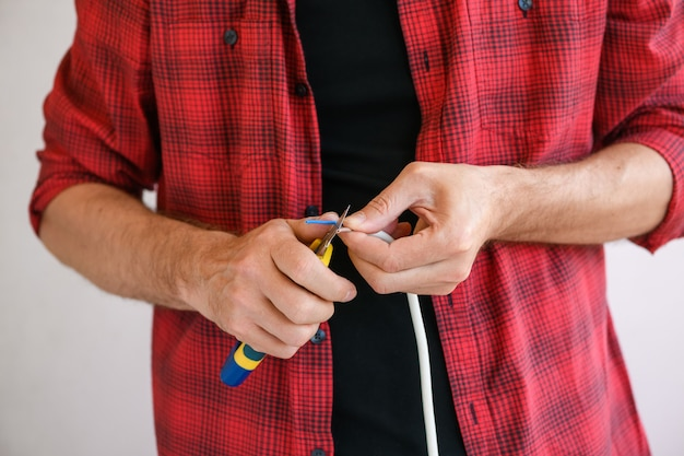 Electrician hands cutting cables wires of extension plug cord with retractable knife at white home background