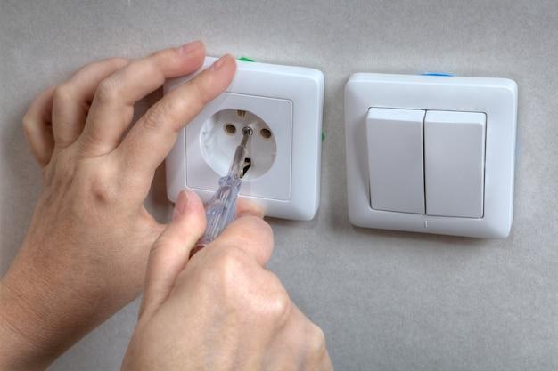 전기 벽면 소켓 및 스크루 드라이버를 사용하여 전등 스위치 수리 중 전기 기사의 손.