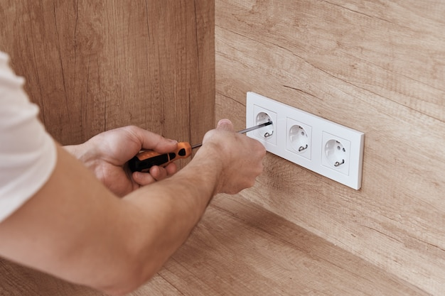 Electrician hands mounting socket in the wall socket installation