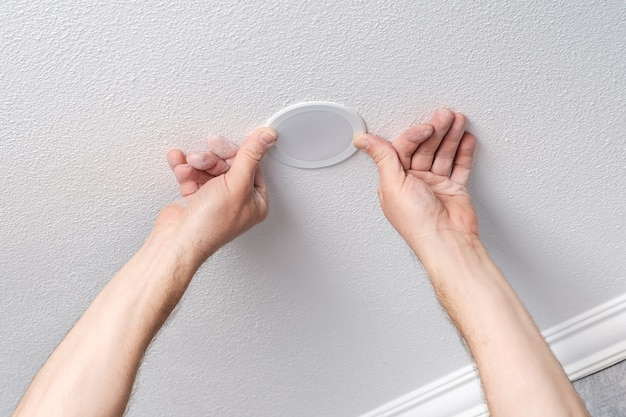 Electrician hands repairs or installs modern led light bulb