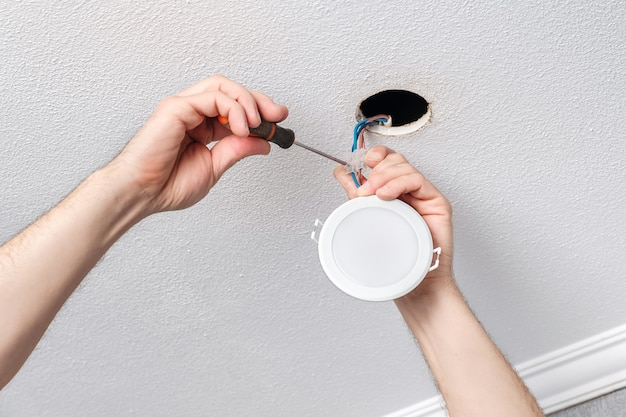 Electrician hands repairs or installs with screwdriver the modern led light bulb