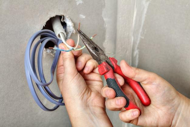 Руки электрика протягивают проводку через отверстие в стене из гипсокартона, зачищают кабели перед тем, как протянуть их.
