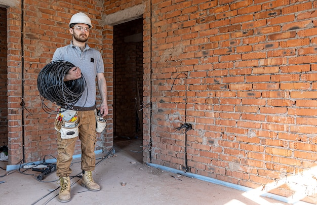 An electrician in a hard hat looks at the wall while holding an electric cable