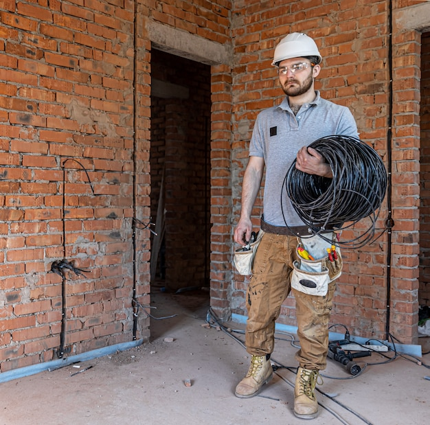 An electrician in a hard hat looks at the wall while holding an electric cable.