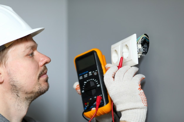 Electrician in helmet measures level electricity. combined electrical measuring instrument, combining several functions. handheld multimeter for basic measurements and troubleshooting at outlet
