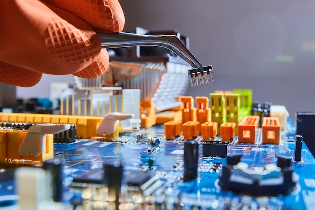 ピンセットでマイクロチップを保持し、マザーボードを修復する電気技師