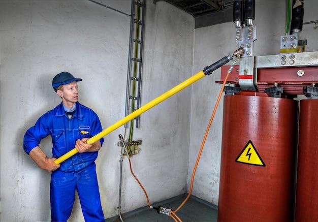 Электромонтажник выполняет заземление понижающего силового трансформатора, для безопасной работы с использованием разрядной ручки, индивидуальное защитное заземление объектов электроэнергетики и линий электропередач.