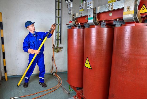 Электрик с помощью заземляющей изолирующей штанги наложит заземление на понижающий трансформатор.