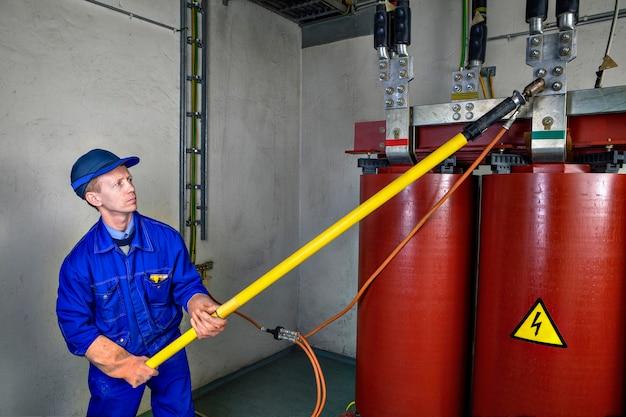 Электрик наложит временное заземление на понижающий силовой трансформатор, для безопасной работы с помощью изолированного стержня.