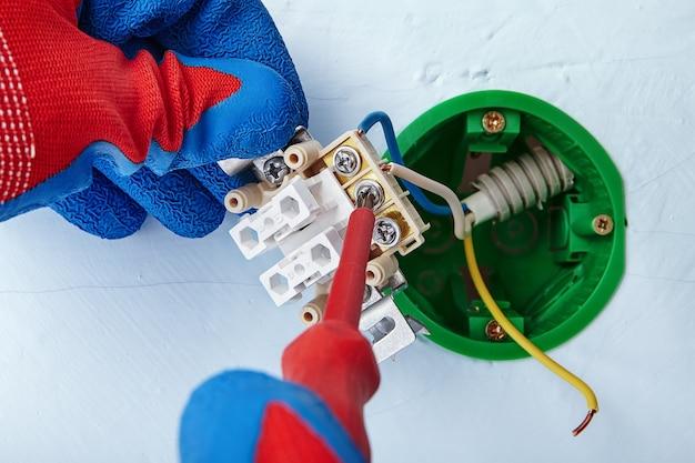 Электрик устанавливает электрическую розетку с помощью отвертки.