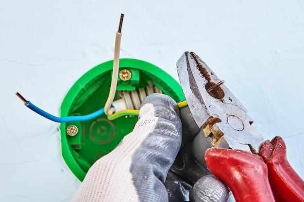 Электрик в защитных перчатках перерезает концы медной проводки круглой розетки для настенного светильника.