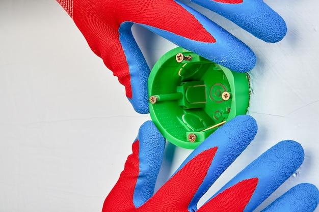 보호 장갑을 착용 한 전기 기사가 벽 조명용 원형 콘센트 상자를 설치하고 있습니다.