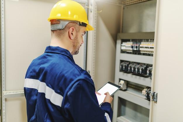 Электрик в защитном костюме и шлеме используя таблетку и пытающся исправить глюк пока стоящ рядом с приборной панелью в заводе тяжелой индустрии.