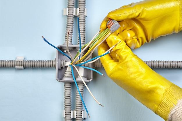 黄色の保護手袋を着用した電気技師は、スプリング端子を使用して配線します