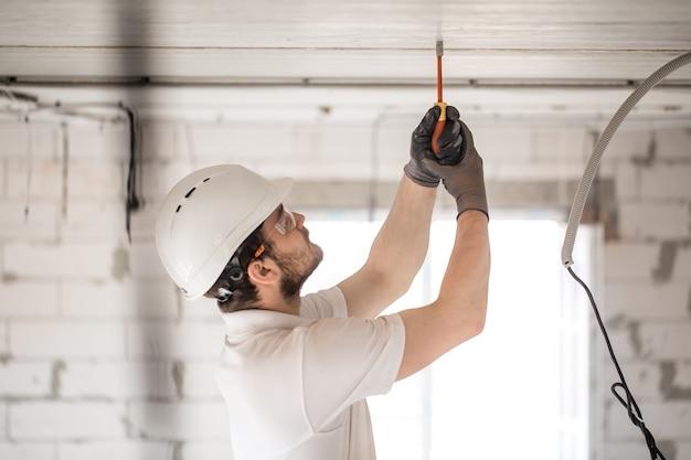 Электрик-установщик с инструментом в руках, работает с кабелем на строительной площадке.