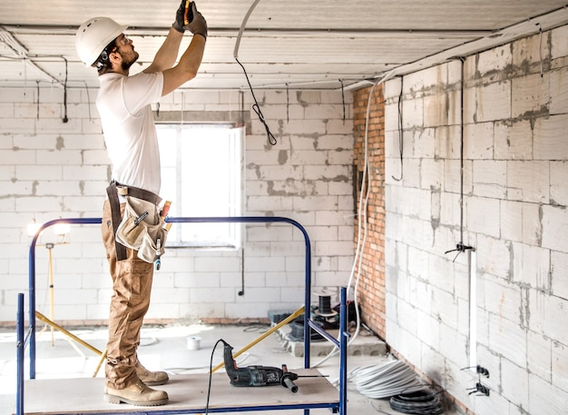 Electrician installer with a tool in his hands, working with cable on the construction site