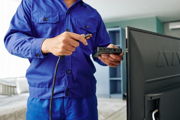 電気技師はデジタルテレビ受信機をインストールします。
